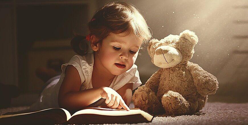 девочка читает мишке
